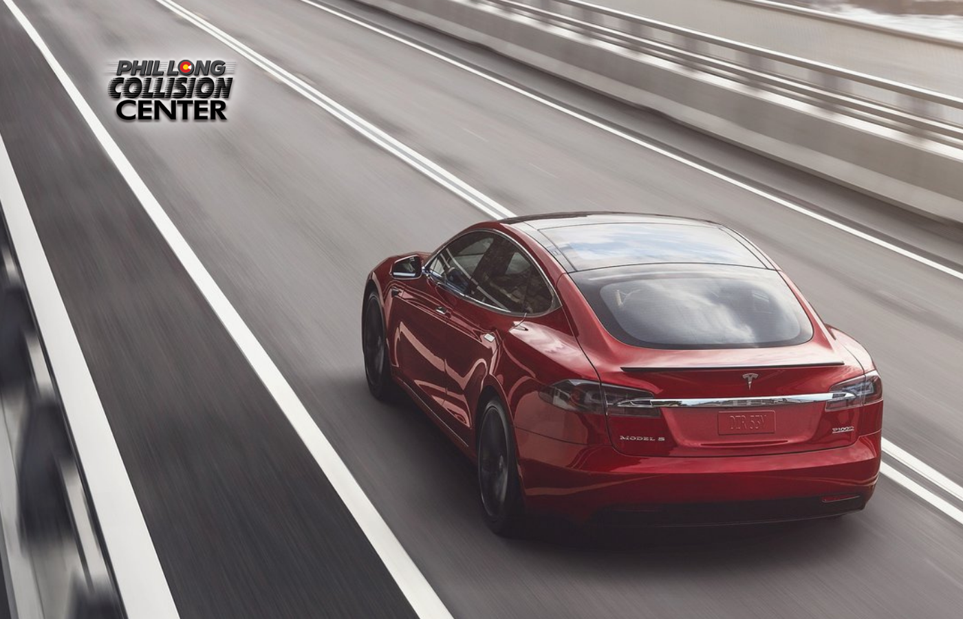 Red 2017 Tesla Model S driving on a highway headed towards an avoidable collision with the Phil Long Collision Center logo in the middle of the road