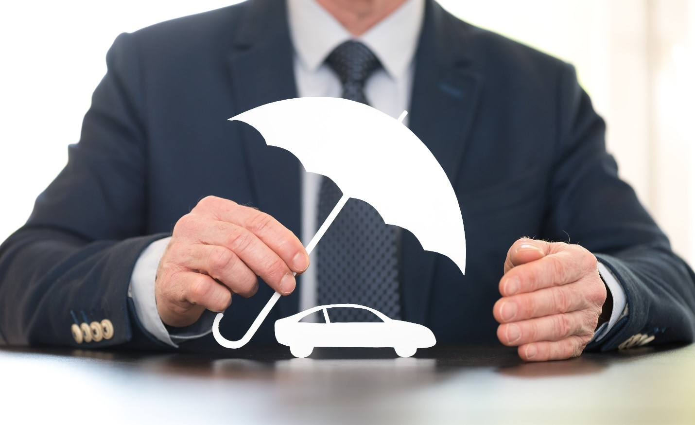 a businessman in a suit and tie holding a white cut-out umbrella over a white cut-out car to indicate car insurance coverage protection against hail damage