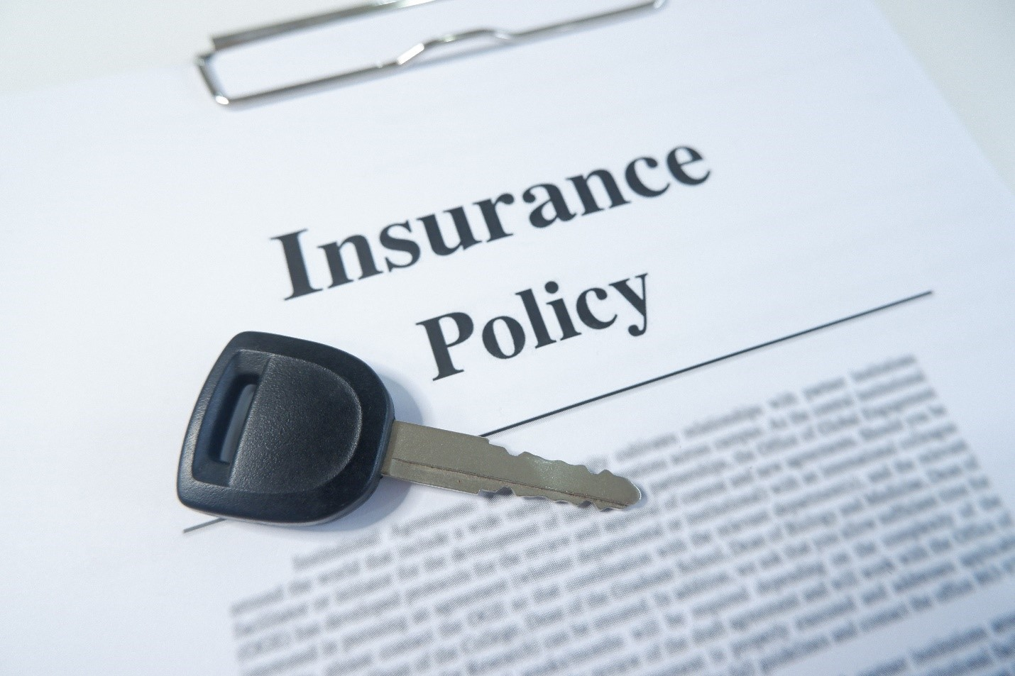 close up of a car insurance policy with a key laying on the top paperwork