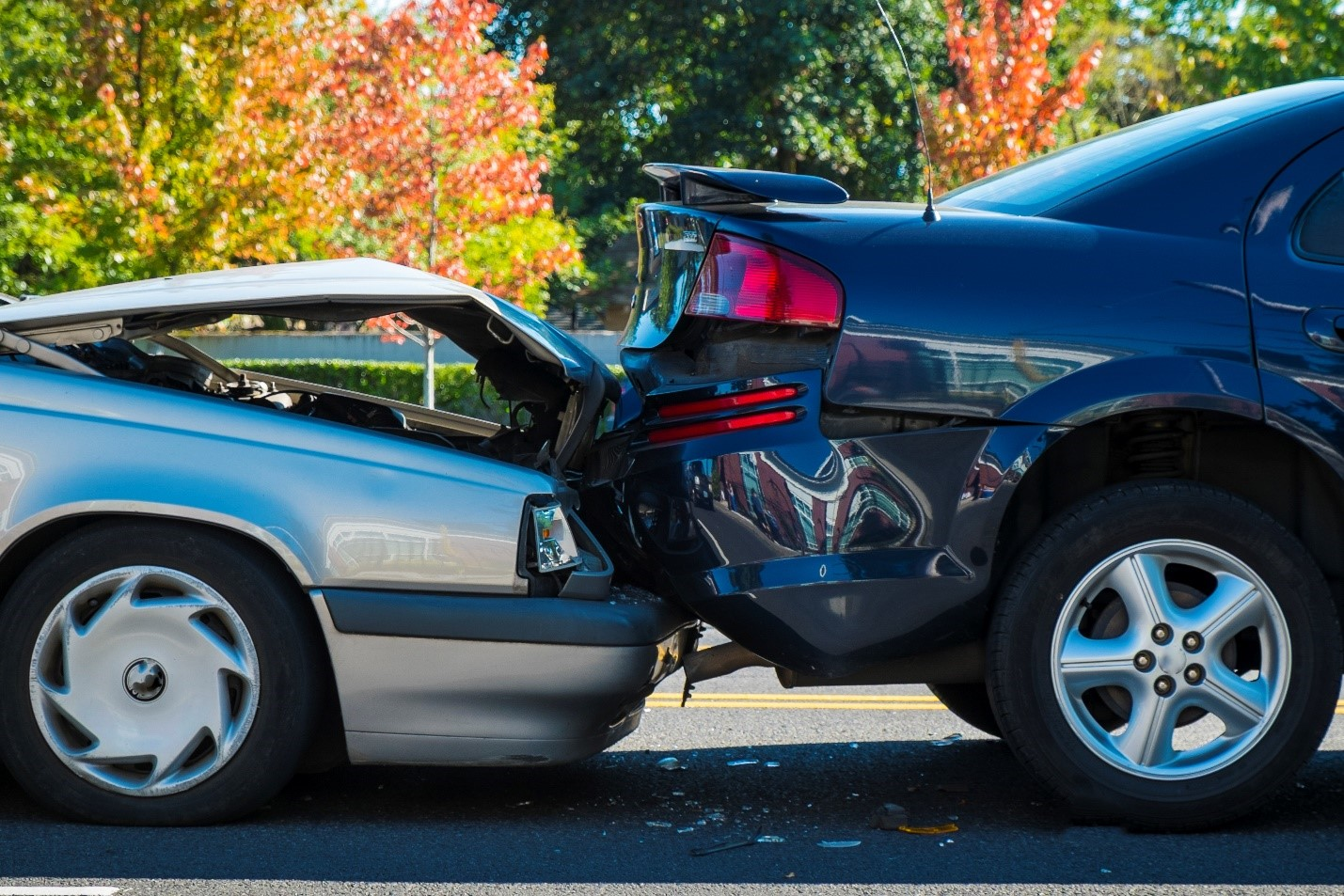 Side view of a front-end and rear-end collision involving two vehicles smashed together
