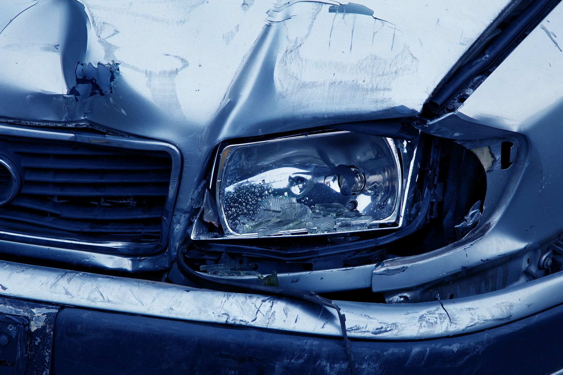 Front end collision showing damage to car bumper grille headlights and hood