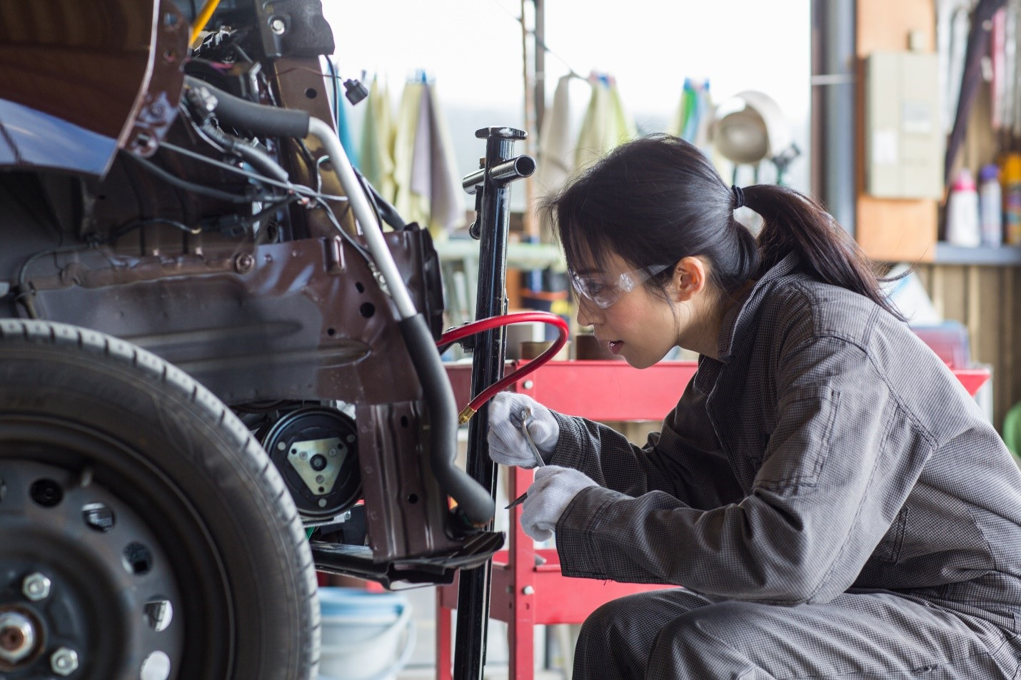 Woman working expertly on a damaged vehicle in a collision repair shop