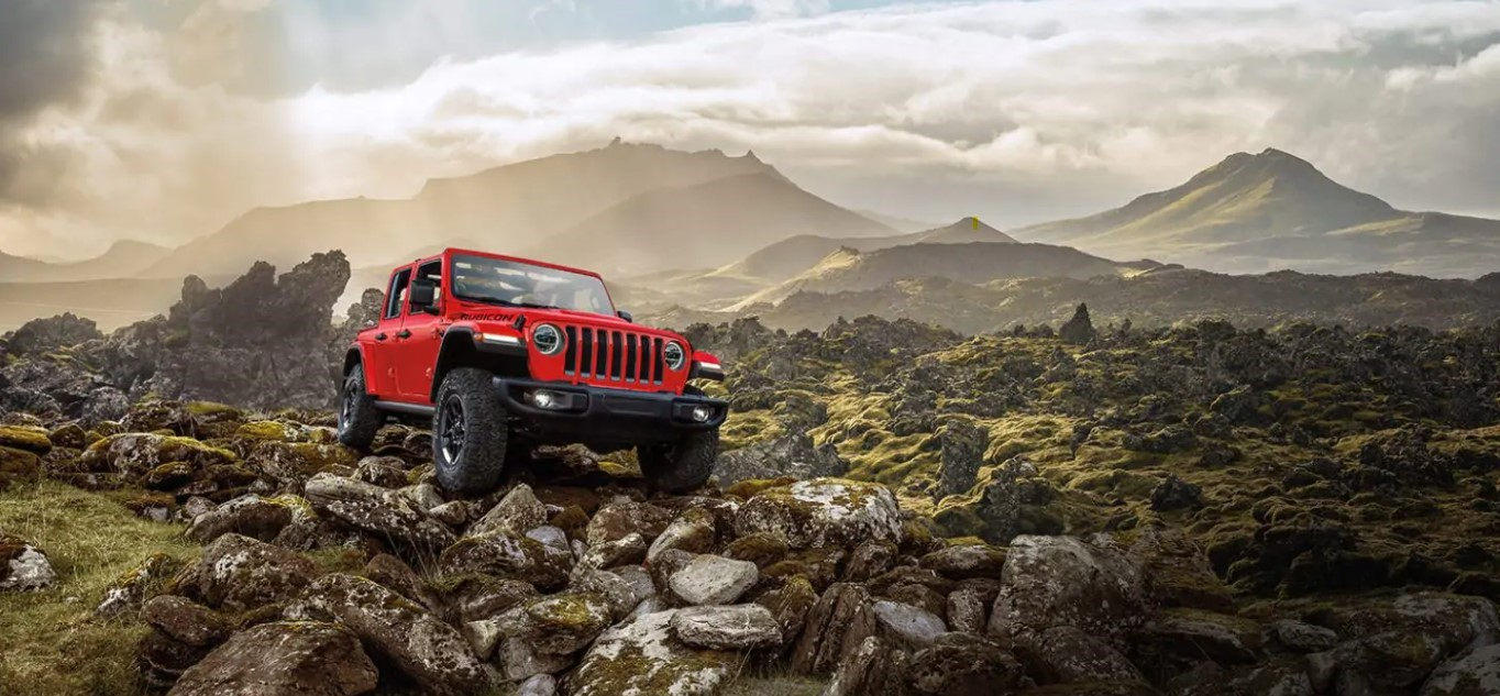 Hero image of a red Jeep in the rocky mountains of Colorado